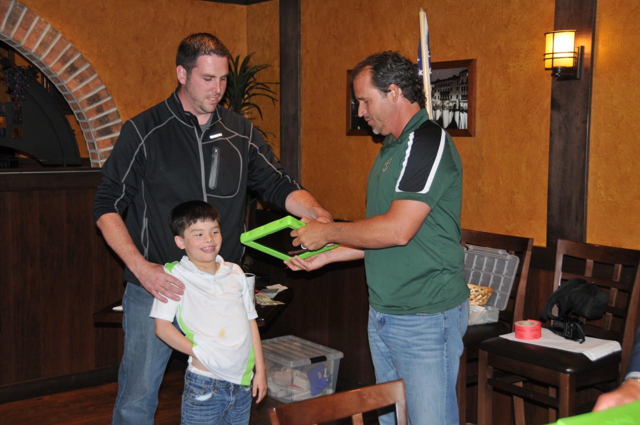 Aiden Kramer receives an iPad from Chris Jacke.